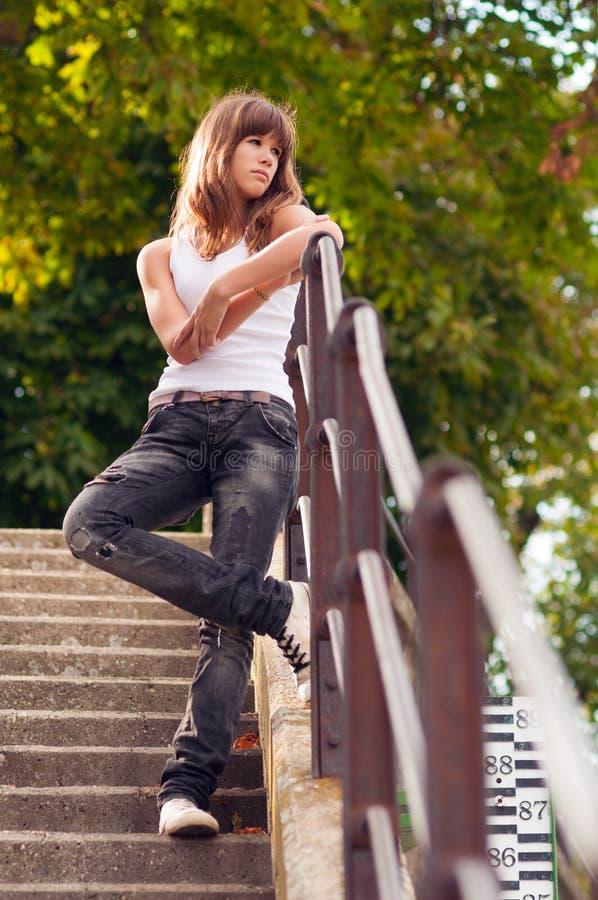 突出在台阶的美丽的孤独的十几岁的女孩 免版税图库摄影