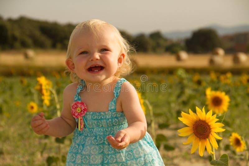 突出在向日葵旁边的婴孩 免版税库存照片