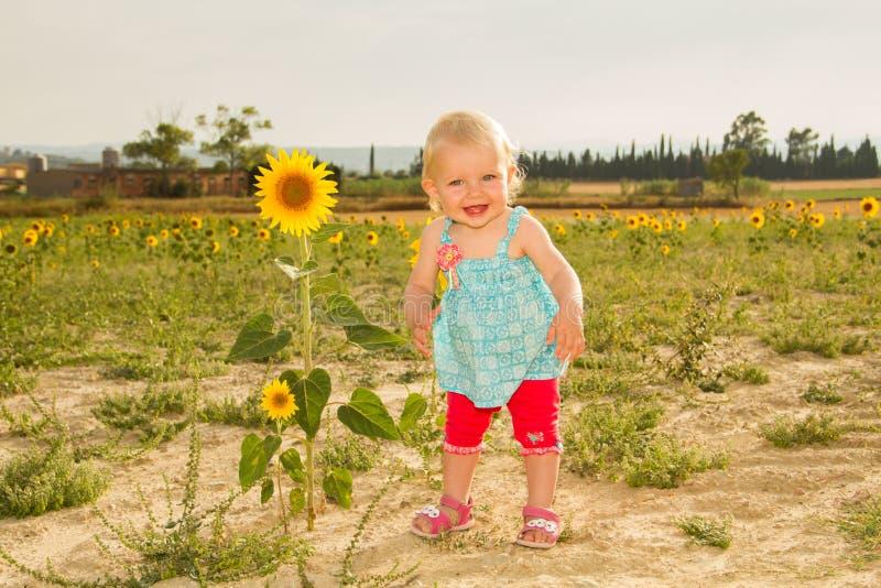 突出在向日葵旁边的愉快的婴孩 免版税库存照片