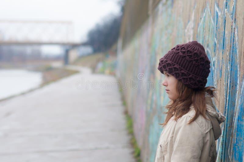 突出在墙壁旁边的孤独的十几岁的女孩 免版税库存图片