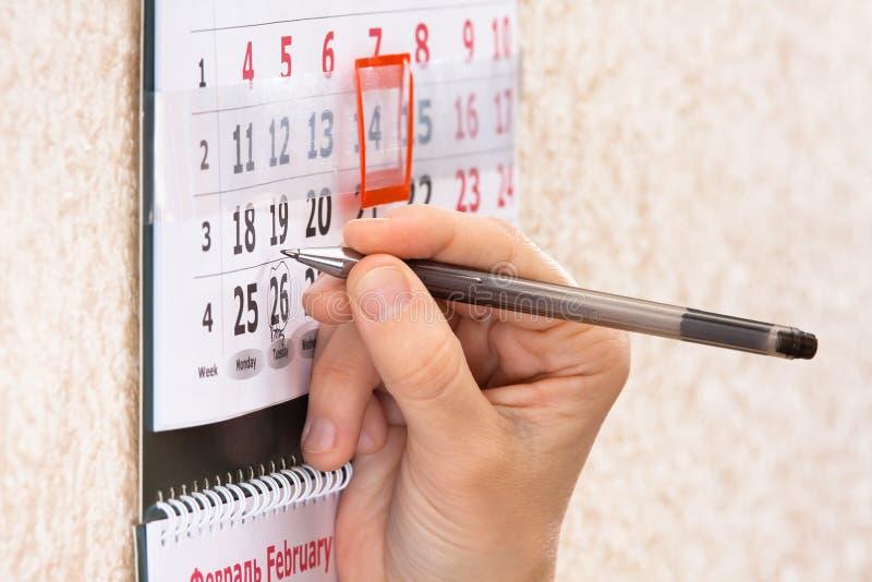 突出在日历的手日期 免版税图库摄影