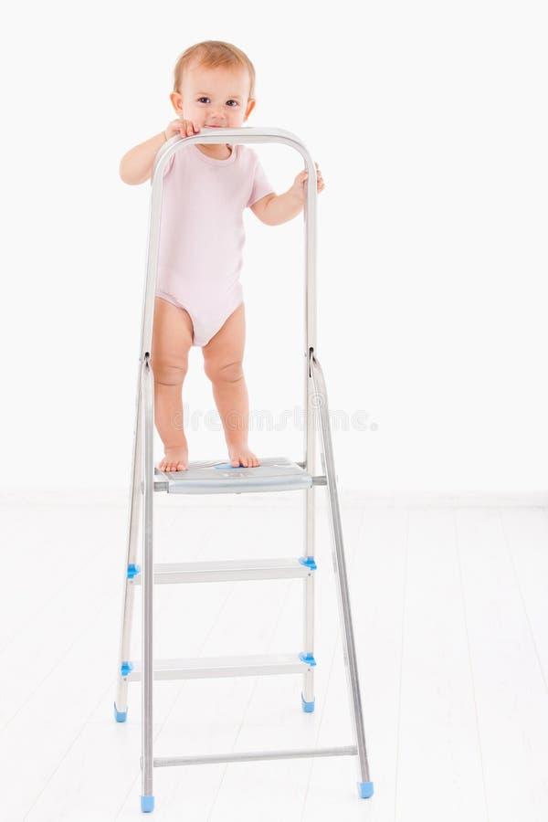 突出在梯子微笑顶部的可爱的女婴 库存图片