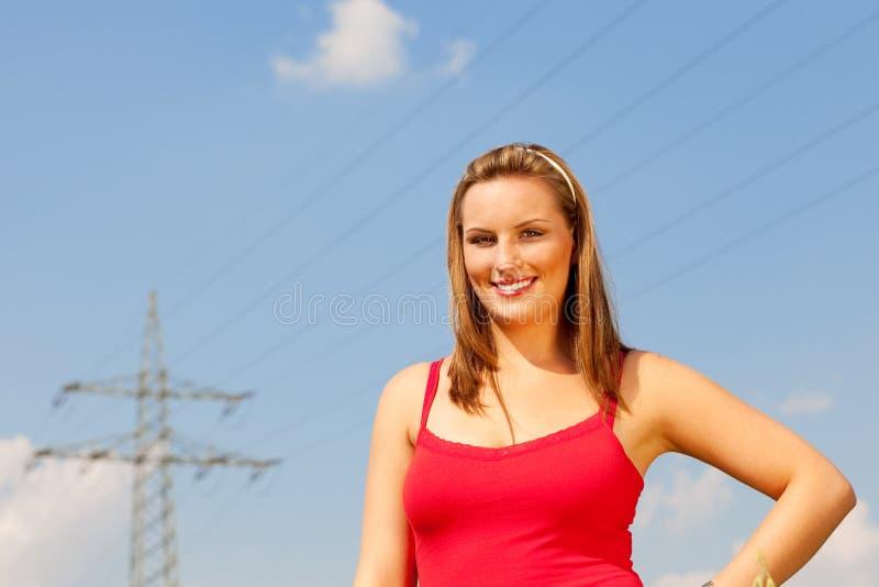 突出在电源杆前面的妇女 库存图片