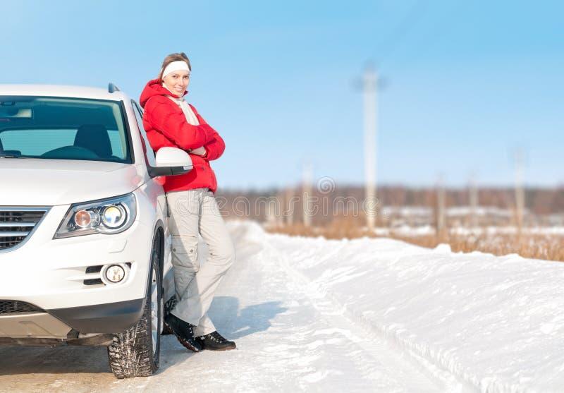突出在空白汽车附近的美丽的妇女在冬天。 图库摄影