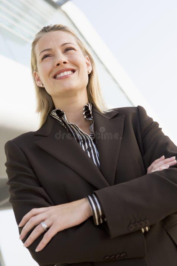 突出大厦的女实业家户外 库存照片