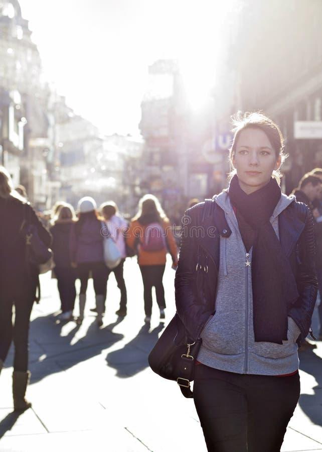 突出从人群的都市女孩在城市街道 免版税库存照片