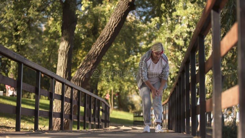 突然感觉在她的腿的中间年迈的妇女抽疯,当跑,健康时 免版税库存照片