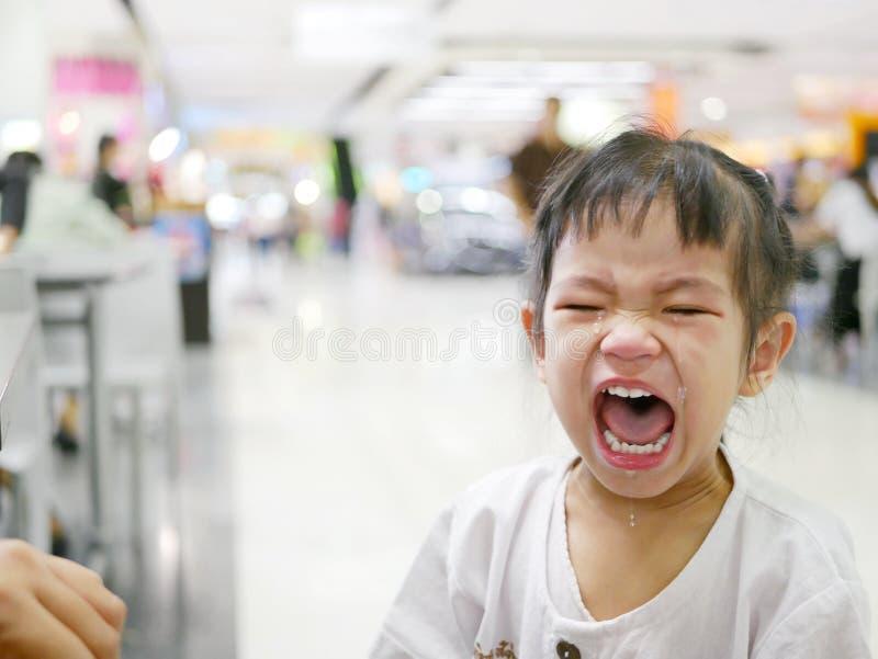 突然的无法控制的爆炸哭泣商城的一个亚裔女婴 库存照片