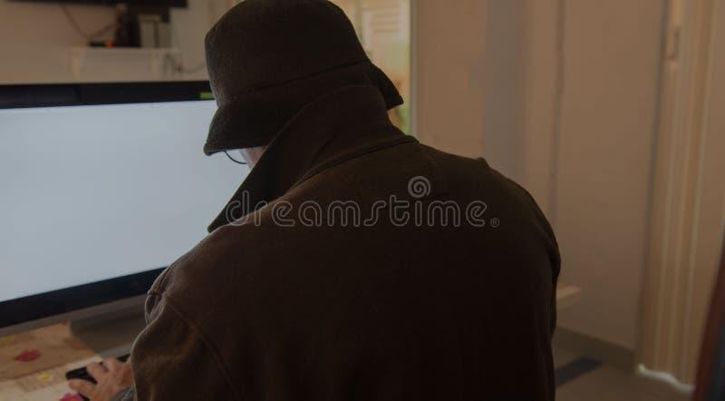 窃取与膝上型计算机的黑客人和计算机信息 图库摄影