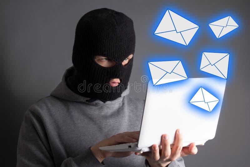 窃取从膝上型计算机的数据或传送垃圾短信信息的黑客 免版税库存照片