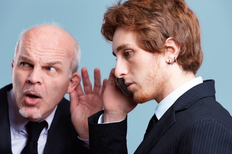 窃听在一名年轻雇员的好奇上司 免版税库存图片