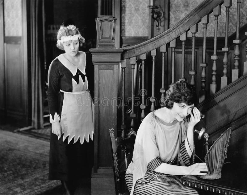 窃听在妇女电话的佣人(所有人被描述不更长生存,并且庄园不存在 供应商保单 库存照片