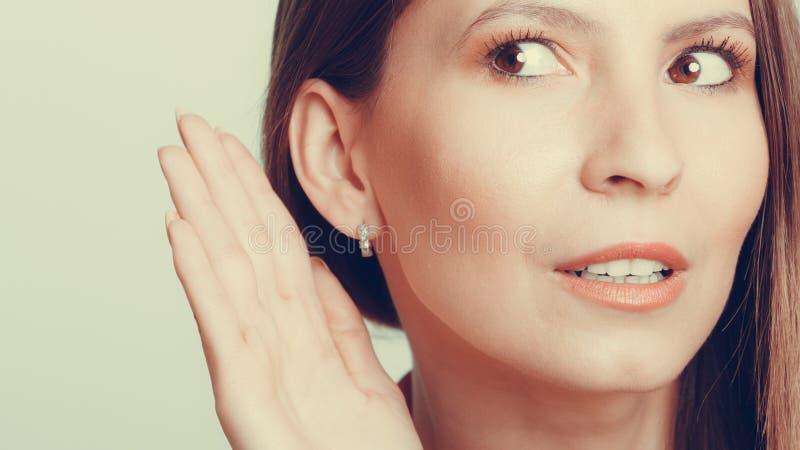 窃听用手的闲话女孩对耳朵 库存图片