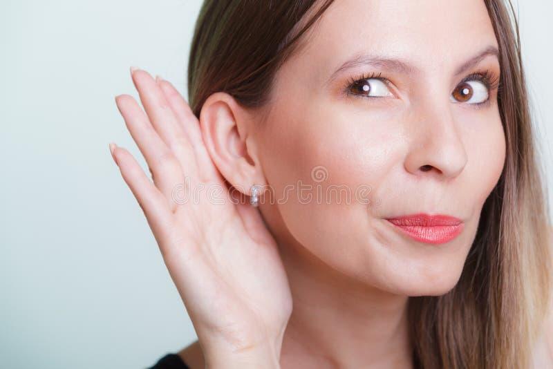 窃听用手的闲话女孩对耳朵 免版税库存图片
