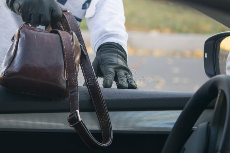 窃贼通过汽车的窗口窃取与文件的一个袋子,由所有者 免版税库存照片