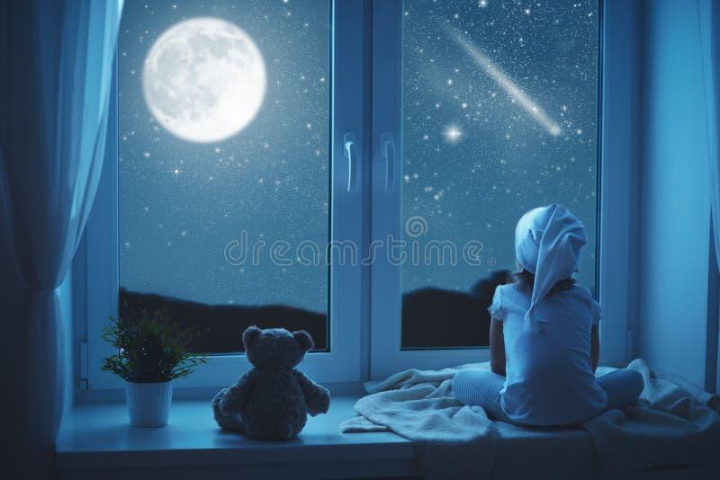 窗口作梦的儿童小女孩和赞赏的满天星斗的天空在 库存照片