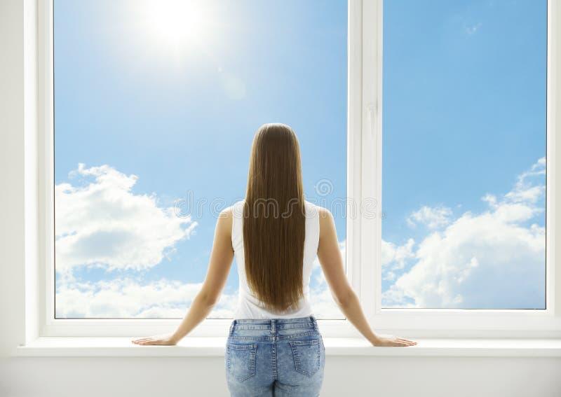 窗口和妇女的女孩站立在白色家的后面观点 库存图片