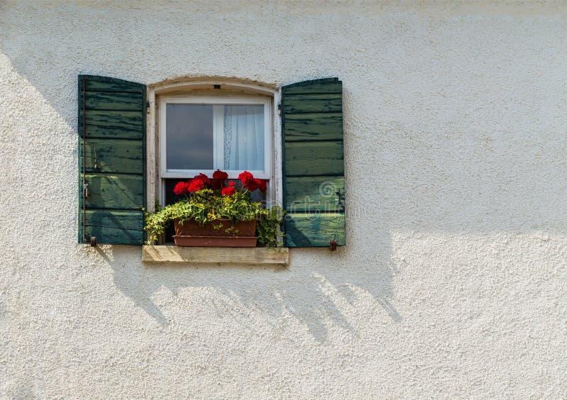 窗口在用花装饰的一个老房子里 免版税库存图片