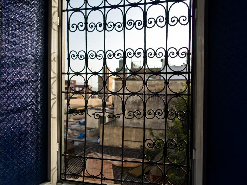 窗口有在麦地那和Bou Inania清真寺屋顶的一个看法在早晨,菲斯,摩洛哥麦地那耸立  库存照片