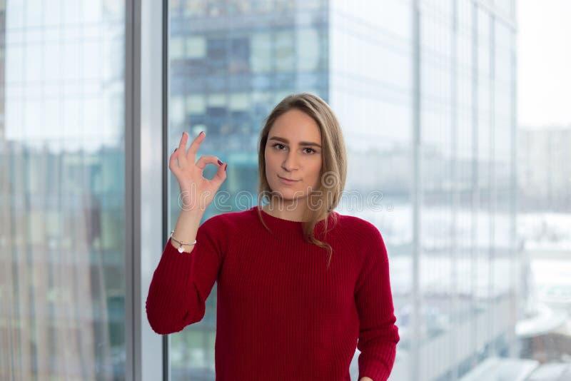 窗口的企业女孩显示一切是好的一个手指 从伙伴的认同 企业交涉 免版税库存照片