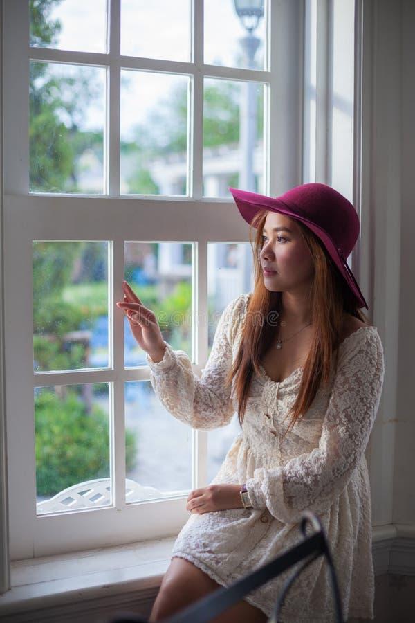 窗口的哀伤的亚裔葡萄酒妇女 免版税库存照片