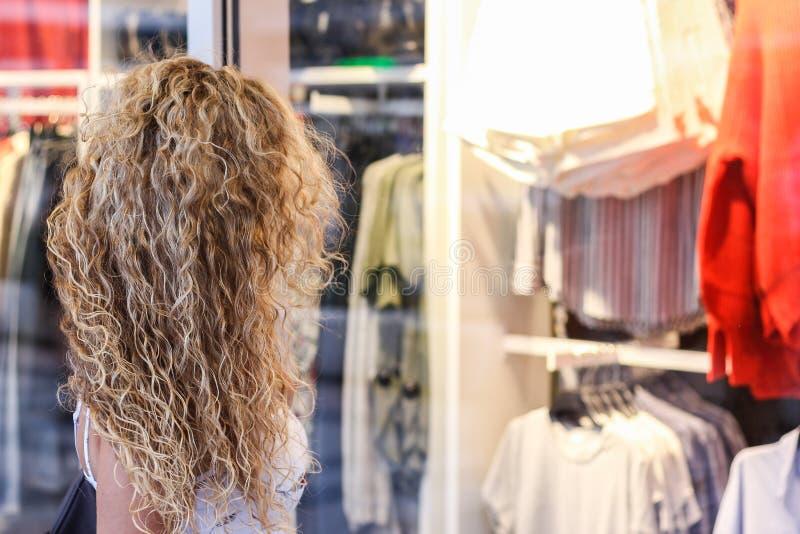 窗口购物-站立在前面的可爱的卷曲白肤金发的女孩 免版税库存图片