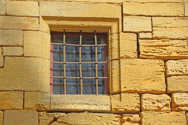 窗户。金色石墙中的中世纪横窗 库存照片