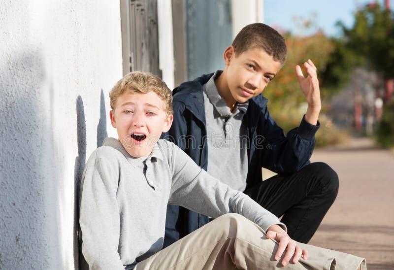 窘迫青少年与耻辱地起反应的朋友 库存图片