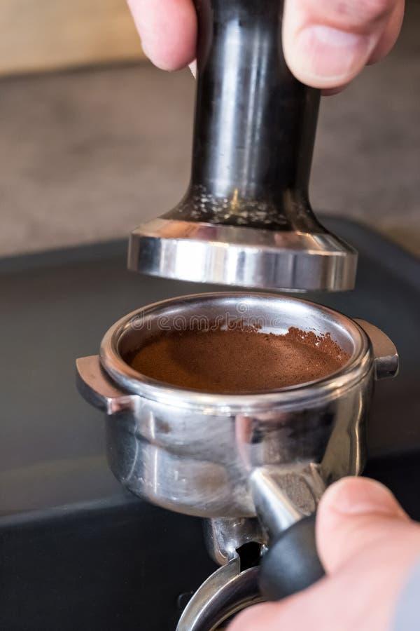 窜改在portafilter的新鲜的被砸紧的咖啡对做espress 库存图片