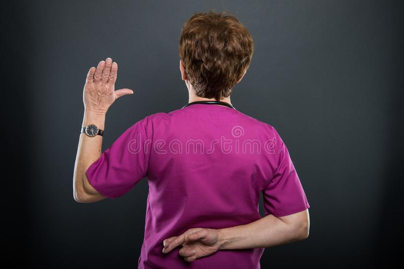 立下假誓言的后面观点的资深夫人医生 库存图片