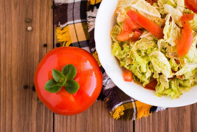 立即可食的菜沙拉、蕃茄和大白菜在一张木桌上 图库摄影