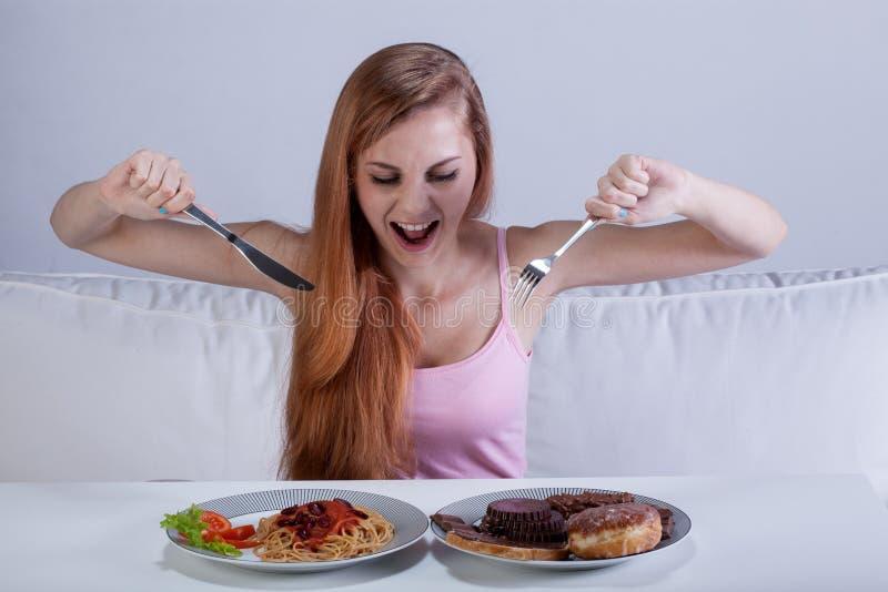 立即吃很多食物的女孩 免版税库存照片