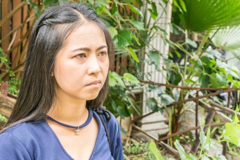 立场的年轻亚裔妇女在家前面的街道上,看与一个严肃的表示的照相机 免版税库存照片