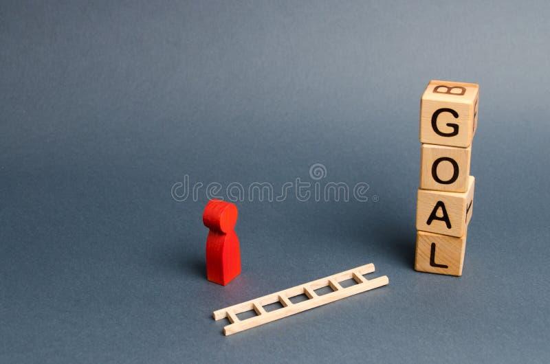 立方体和一个人的一个红色图塔与题字目标的在下落的梯子附近站立 达到目标的概念 免版税库存照片
