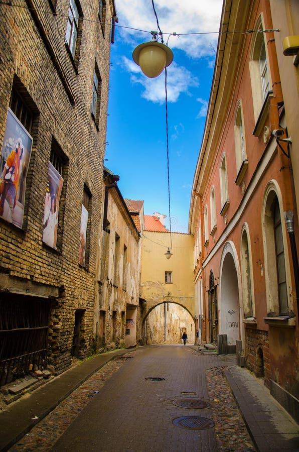 立陶宛维尔纽斯 — 2015年4月20日:老城狭窄的街道,有拱门,建筑 免版税库存照片