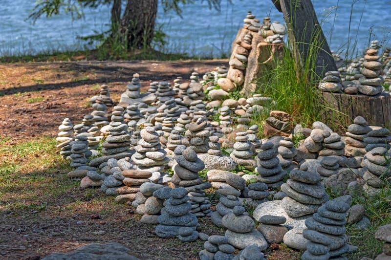 竖石纪念碑 石头,反对水的石雕塑金字塔  在小山堆的石标石头 库存照片