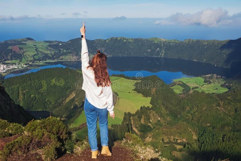 站在山湖边的年轻女游客 免版税库存照片