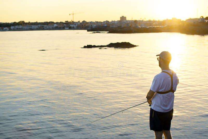 站在海边的渔夫,在夕阳下钓鱼 运动员把钓竿和卷轴放在钩状鱼里 旋转 库存图片
