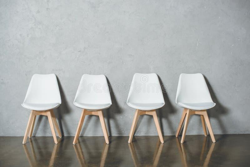 站在队中在大厅里的工作面试的白色空的椅子 库存图片