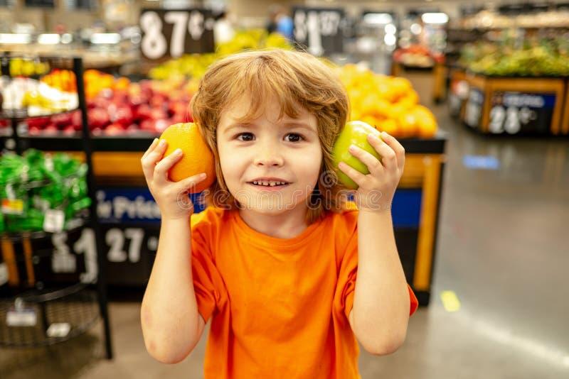 站在食杂处,一个小可爱男孩,手推车里摆满新鲜有机蔬菜和水果 库存图片
