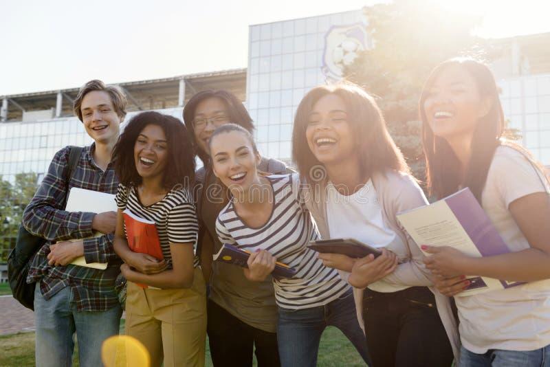 站立不同种族的小组年轻快乐的学生户外 图库摄影