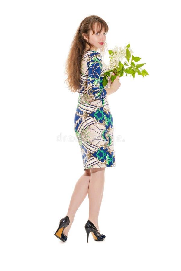 站立与丁香的可爱的女孩在手上 库存图片