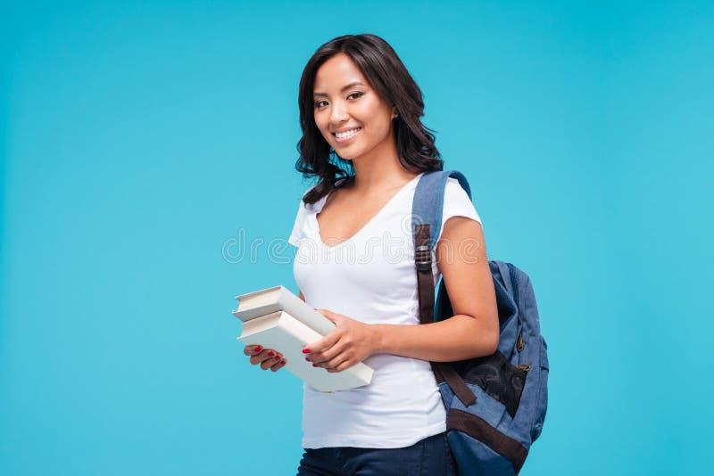 站立与书的微笑的年轻亚裔学生女孩 免版税库存图片
