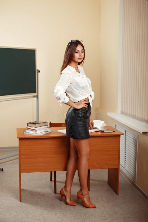 站立与书的美丽的妇女老师近的桌 免版税图库摄影