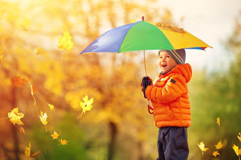 站立与伞的孩子在美好的秋季天 库存图片