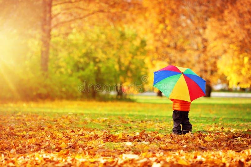 站立与伞的孩子在美好的秋季天 免版税库存照片