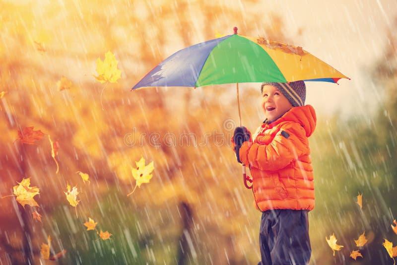 站立与伞的孩子在美好的秋季天 免版税库存图片