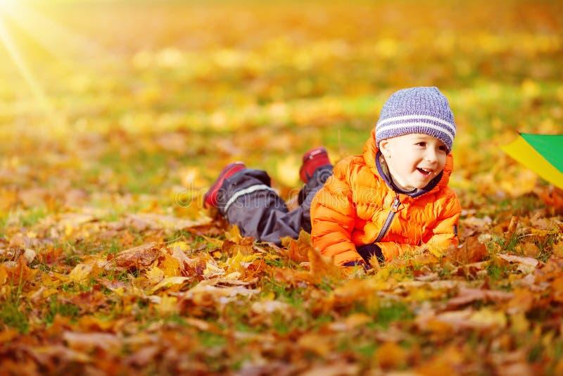 站立与伞的孩子在美好的秋季天 免版税图库摄影