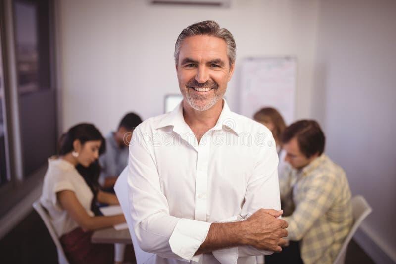 站立与同事的成熟商人在背景中 免版税库存照片