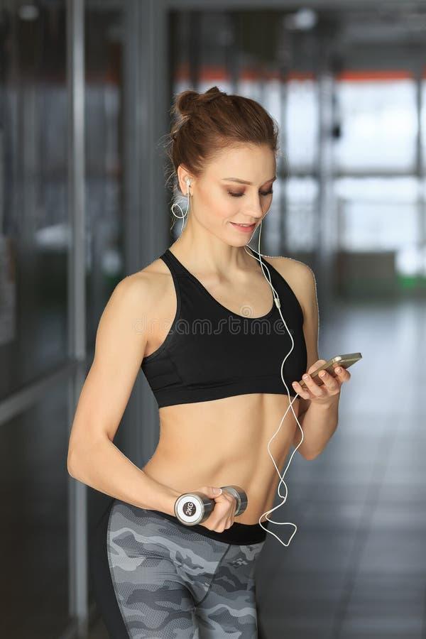 站立与哑铃和看电话的美丽的健身妇女 免版税库存图片